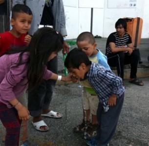 Προσφυγόπουλα προσπαθούν να ξεδιψάσουν πίνοντας νερό από το λάστιχο στο κέντρο φιλοξενίας του Ελληνικού