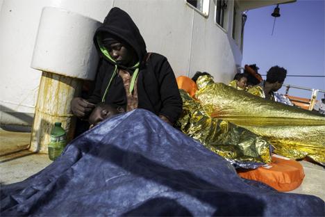 Η Fatima, που ξέφυγε από το ξέσπασμα του ιού Έμπολα στη Σιέρα Λεόνε, κρατάει στην αγκαλιά της τον γιο της Daniel πάνω στο σκάφος έρευνας και διάσωσης Sea Watch στη Μεσόγειο το 2016. © UNHCR/Hereward Holland
