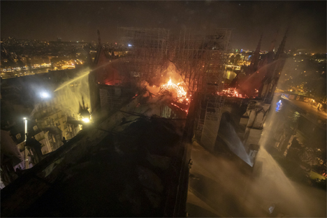 This aerial photo provided Tuesday April 16, 2019 by the Paris Fire Brigade shows Notre Dame cathedral burning, Monday April 15, 2019. Experts assessed the blackened shell of Paris' iconic Notre Dame Tuesday morning to establish next steps to save what remains after a devastating fire destroyed much of the cathedral that had survived almost 900 years of history. (Benoit Moser/BSPP via AP)