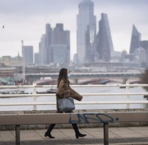 Γυναίκα με μάσκα περπατά στο Λονδίνο  VICTORIA JONES / ASSOCIATED PRESS