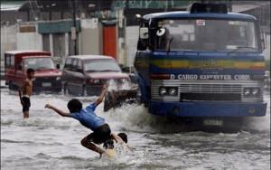 Παιδιά παίζουν σε πλημμυρισμένο δρόμο στη Μανίλα μετά από καταρρακτώδεις βροχές. - Photo: EPA/MIKE F. ALQUINTO